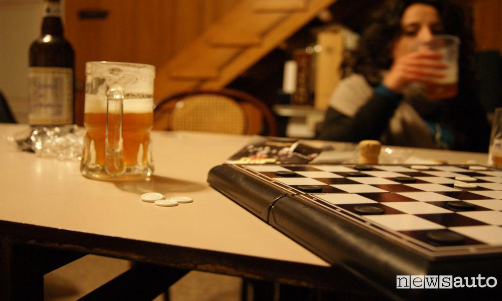 Ragazza che beve birra durante una partita a scacchi