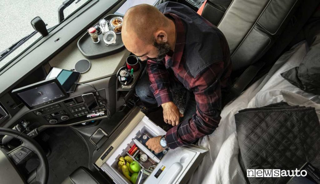Camionista o autista in pausa e sosta di relax con bevande e cibi freschi dal frigorifero
