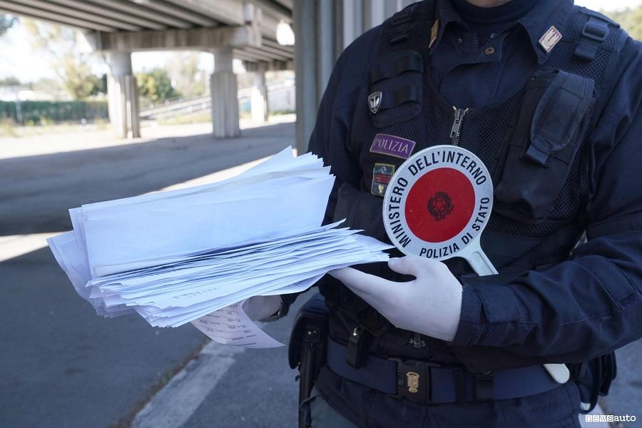 Un agente di Polizia con la paletta in mano mentre controlla la validità della polizza assicurativa